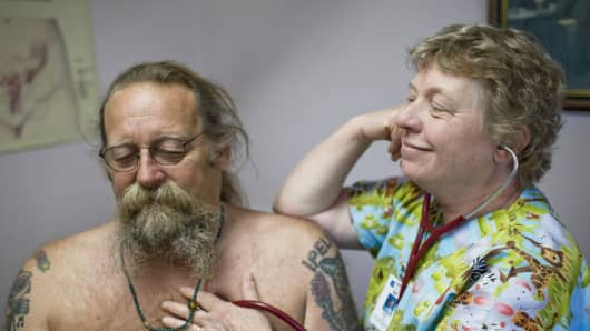 Mary Fey examines Jef Jalof, 61, at the Dexter Clinic run by PeaceHealth Medical Group outside Eugene, Ore.