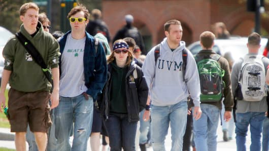 Students walk across campus at the University of Vermont in Burlington, Vt.