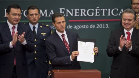 Mexican President Enrique Pena Nieto (C) shows the bill of constitutional reform that would allow oil company Pemex to partner with private firms.
