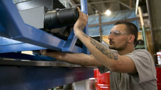 Employee Mike Flynn installs air coolers on a stand in the subassembly area at the Ellicott Dredges LLC manufacturing facility in Baltimore, Maryland.