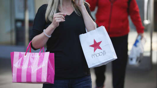 A shopper carries a purchase from Macy's along the Magnificent Mile shopping district in Chicago, Illinois.