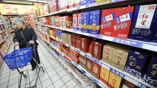 A woman browses bottles of baijiu displayed at a store in Beijing.