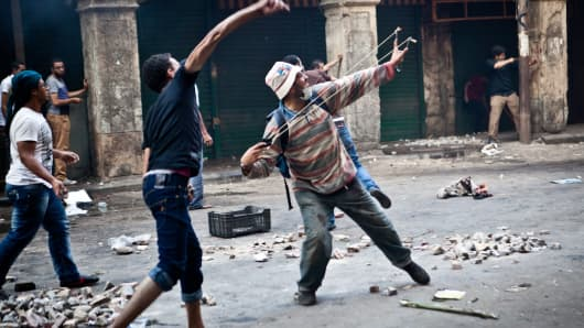 Supporters of ousted president Mohamed Morsi throw stones as they clash with security officers in Cairo's Ramses Square on Friday.