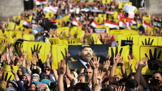 Protestors hold signs during a demonstration condemning the recent deadly military crackdown on supporters of ousted Egyptian President Mohamed Morsi protesters in Cairo on Saturday.