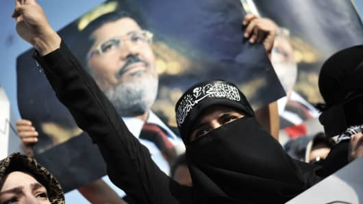 A woman protestor chants slogans in front of a poster of Egypt's ousted president Mohamed Morsi during a demonstration condemning the recent deadly military crackdown on pro-Morsi protesters in Cairo Saturday.