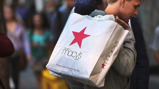 A shopper carries a Macy's shopping bag