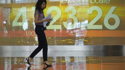 A woman walks past an Indonesian stock exchange display board in Jakarta on August 20, 2013.
