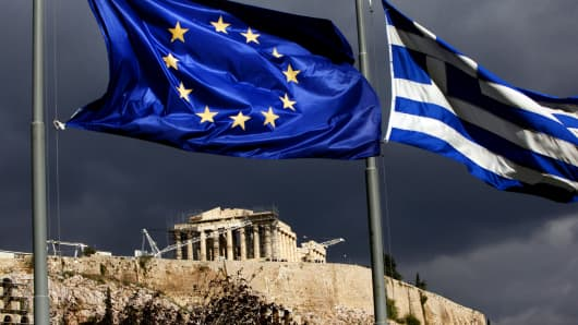 A European Union flag, left, and Greek national flag fly near the Parthenon temple on Acropolis hill in Athens, Greece.