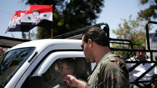 A Syrian military soldier checks a man's identification at a check point on Baghdad street, in Damascus, Syria, Wednesday, Aug. 21, 2013.