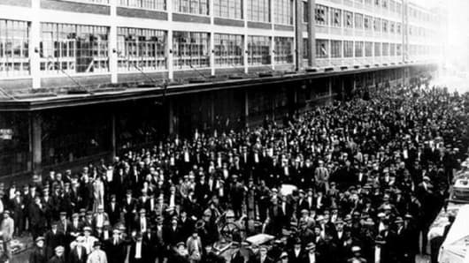 In 1914 after Ford announced it was raising worker's pay, thousands swamped the Highland Park plant to apply for jobs.
