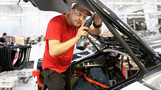 Tesla employee works on a Tesla Model S sedan