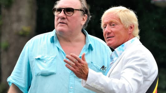 The mayor of Estaimpuis, Daniel Senesael (R), welcomes French actor Gerard Depardieu before a ceremony held in his honor at the Chateau Bourgogne in Estaimpuis on August 24, 2013.