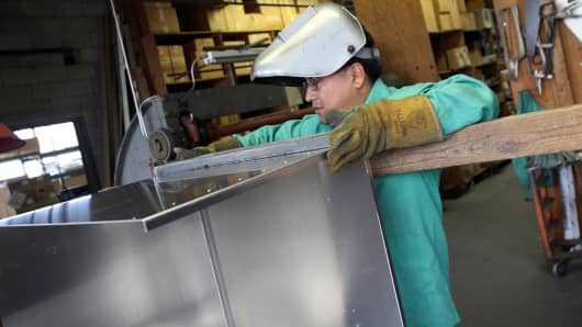 A worker prepares to weld an aluminum case at the Aluminum Case Company in Chicago.