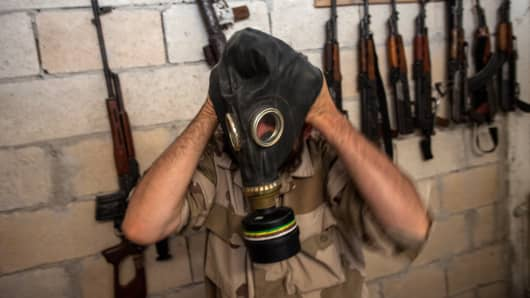 A Syrian rebel tries on a gas mask seized from a Syrian army factory in the northwestern province of Idlib.