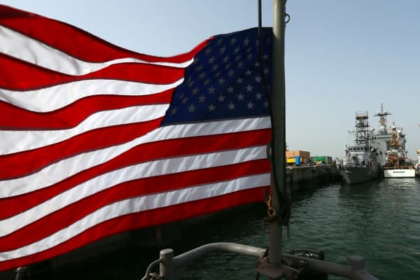 An American flag flies near US Navy boats docked at Bahrain's Salman port in the capital Manama, on May 12, 2013