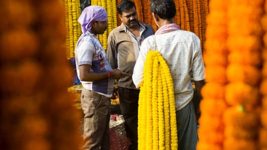 An Indian vendor speaks with a customer at a flower market in New Delhi in August.