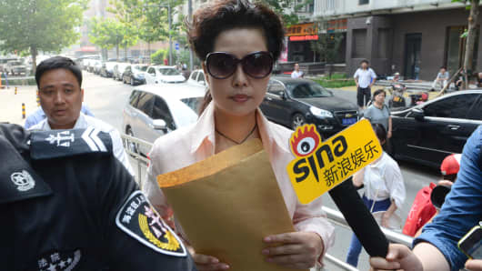 Picture taken on August 20, 2013 shows Meng Ge (C), mother of Li Tianyi, the son of a Chinese general charged with rape, according to state media, outside Haidian court in Beijing.