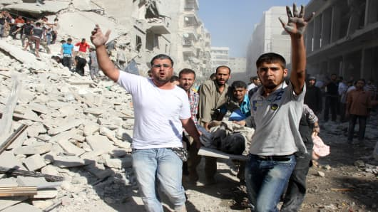Syrian men evacuate a victim following an air strike by regime forces in the northern city of Aleppo on August 26, 2013.