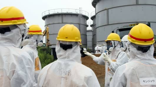 Japan's nuclear watchdog members, including Nuclear Regulation Authority members in radiation protection suits in Fukushima