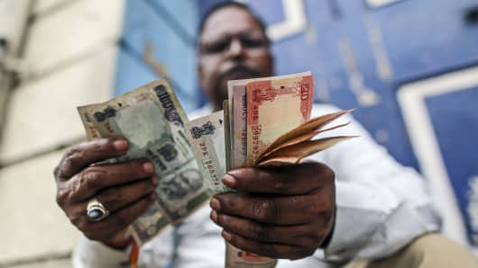 A man counts Indian rupee notes near the Bombay Stock Exchange building.