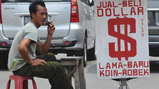An Indonesian man waits for customers at a street money changer in Jakarta on August 28, 2013.