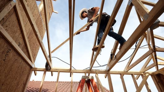 A worker builds a new home at a housing development in Phoenix, Arizona.
