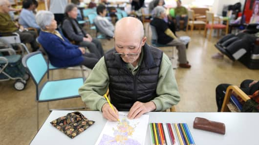 An elderly man does a coloring exercise at a day care facility, Japan.