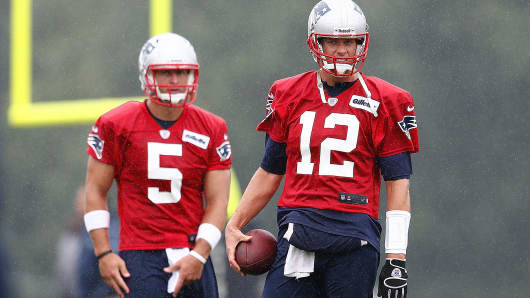 Tom Brady #12 and Tim Tebow #5 look on during the first day of New England Patriots training camp at Gillette Stadium in Foxboro, Mass.