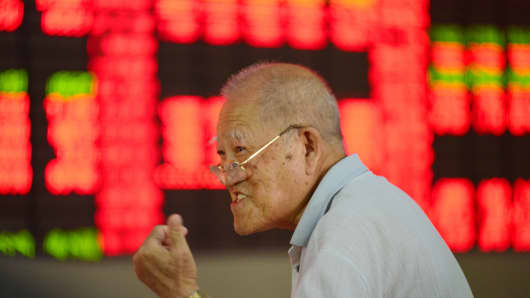 An investor watches the electronic board at a stock exchange hall in Shanghai, China.