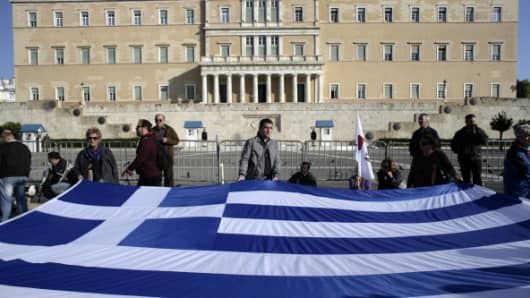 Protestors stand with a Greek flag outside the Greek parliament during an anti-austerity protest.