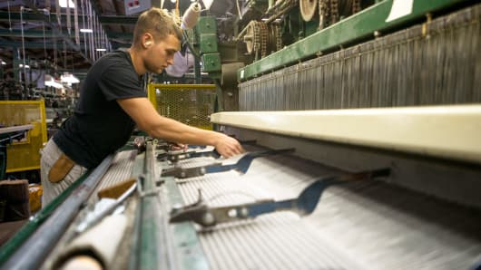 An employee adjusts an industrial-sized loom as it creates a roll of carpet at the Bloomsburg Carpet Industries Inc. in Bloomsburg, Pennsylvania.