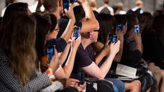 Fashion goers recording the Marc Jacobs fashion show during MBFW Spring 2014 at Pier 57 in New York.