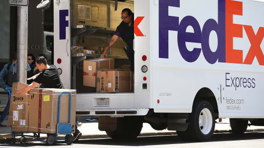 FedEx workers unload packages from a delivery truck in San Francisco, California.