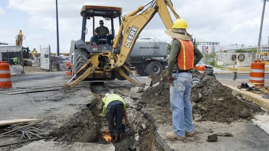 Construction workers dig a trench on a waterfront street in Old San Juan, Puerto Rico.