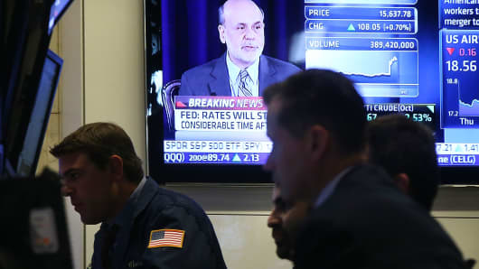 Fed Chairman Ben Bernanke, speaking at a news conference, is seen on a TV screen on the floo