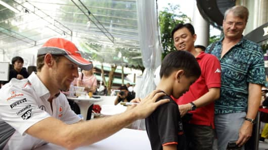 Formula One driver Jenson Button (L) McLaren greets fans and signs autographs during 'The One Legacy Tour' on September 18, 2013 in Singapore.