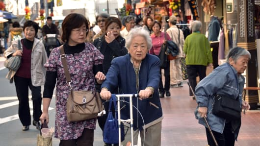 Elderly people stroll down a shopping precinct in Tokyo.
