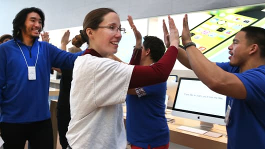 Apple Store employees greet customers who are purchasing the new iPhone on Sept. 20, 2013, in Palo Alto, Calif.