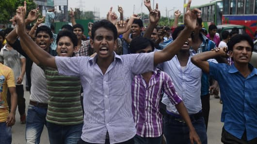 Bangladeshi garment workers shout slogans during a protest in Dhaka on September 23, 2013.