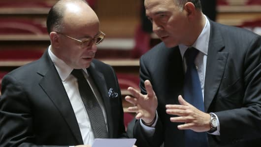 French Finance minister Pierre Moscovici (R) speaks with French Junior Minister for Budget Bernard Cazeneuve during a session of questions to the government at the French Senate in Paris on September 19, 2013.
