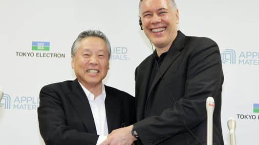 Gary Dickerson, chief executive officer of Applied Materials., right, shakes hands with Tetsuro Higashi, chairman of Tokyo Electron Ltd., during a news conference in Tokyo, Japan, on Tuesday, Sept. 24, 2013.