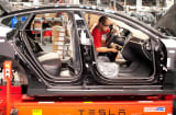 An employee works on a Telsa Model S sedan on an assembly line at the company's assembly plant in Fremont, California.