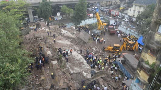 Firefighters and rescue workers are seen working at the site of the building collapse in Mumbai on September 27, 2013.