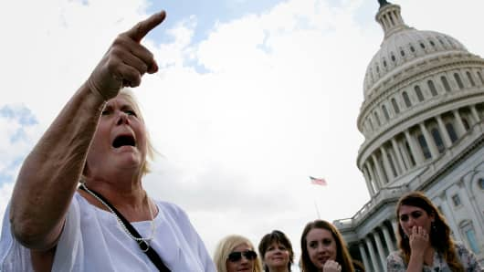 Catheryn Carroll, of Washington DC, berates members of the House Republican caucus while they hold a press conference on the steps of the U.S. Senate September 29, 2013 in Washington, DC.