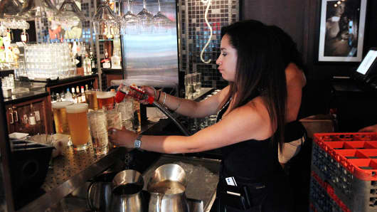 A waitress prepares a drink order Bar Louie restaurant located in the River North neighborhood of Chicago.