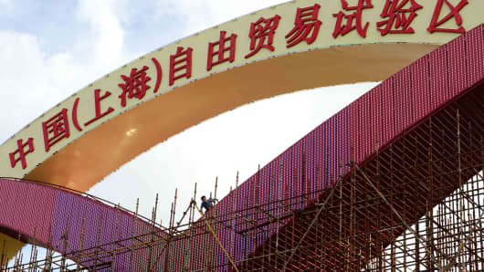 A laborer working on a large sign reading China (Shanghai) Pilot Free Trade Zone on a gate of the Shanghai Waigaoqiao Free Trade Zone.