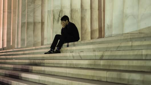 A man sits in front of the Lincoln Memorial on Tuesday, hours after the government shut down nonessential services.