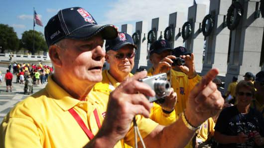 Korean War veteran Bill Bakley, and Vietnam War veterans Norman Tjelmeland and Stanley Twedt  snap pictures at the World War II Memorial.