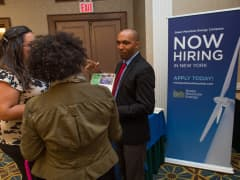 Jose Mosquea, a recruiter for Green Mountain Energy, right, speaks to job seekers during an employment fair hosted by Premium Job Fairs in New York.