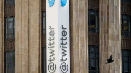 A bird flies past Twitter Inc. signage displayed outside the company's headquarters in San Francisco, California.
